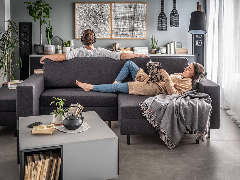 szara kanap zdwoma osobami stojąca na podłodze zsurowego betonu obok stolika kawowego