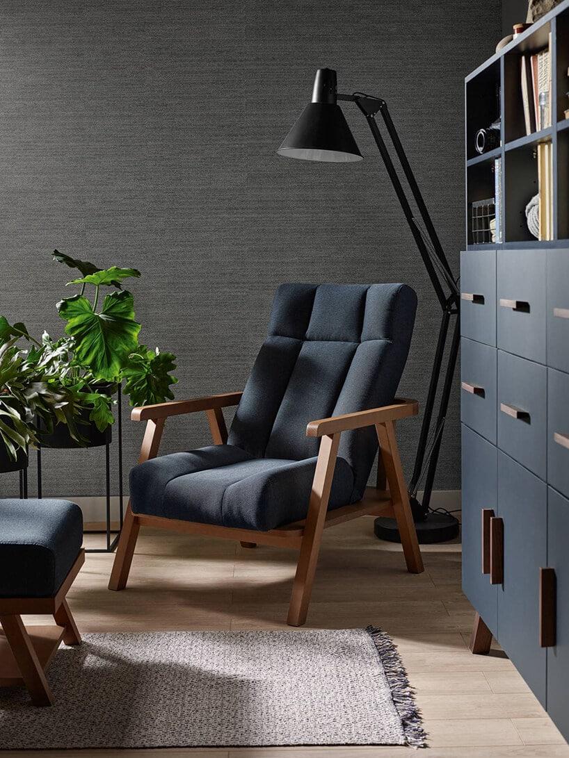 wygodny fotel wkolorze ciemno niebieskim zdrewnianym stelażem oraz wiszącą czarną lampką nad