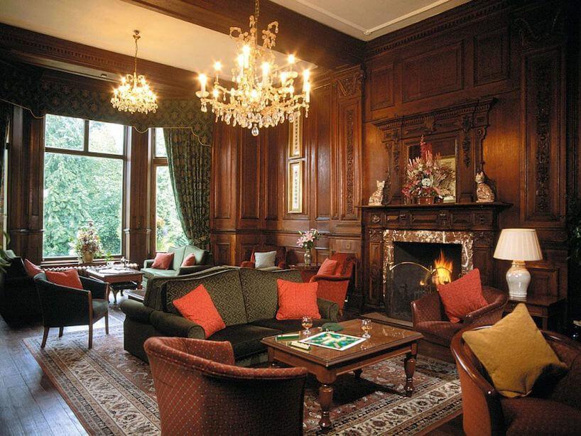 eleganckie wnętrze wstylu angielskim wykończony ciemny brązowym drewnem ze zdobieniami zdużym kominkiem ciemnymi brązowymi izielonymi sofami ifotelami