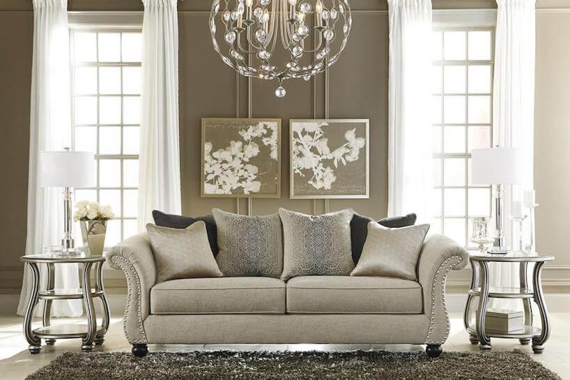 jasne eleganckie wnętrze wstylu angielskim beżowa sofa pomiędzy dwoma metalowymi stolikami pod żyrandolem ze szklanymi ozdobami