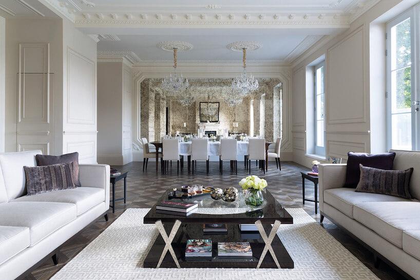 białe eleganckie wnętrze wstylu angielskim zciemną podłogą dwie białe sofy przy czarnym stoliku na tle stołu zbiałymi krzesłami wczęści jadalnej