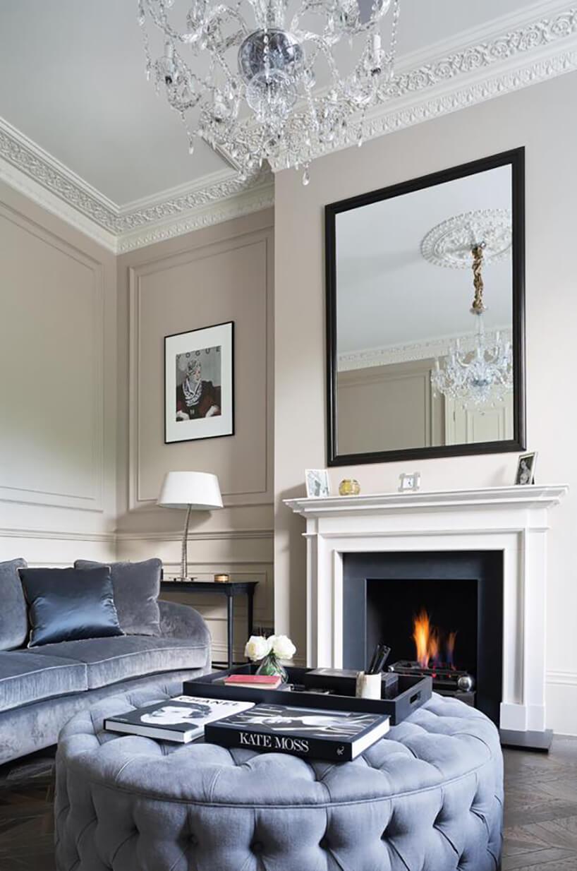 eleganckie wnętrze wstylu angielskim zniebieską duża plisowaną pufą natle niebieskiej sofy iciemnego kominka zbiała zabudową pod dużym lustrem