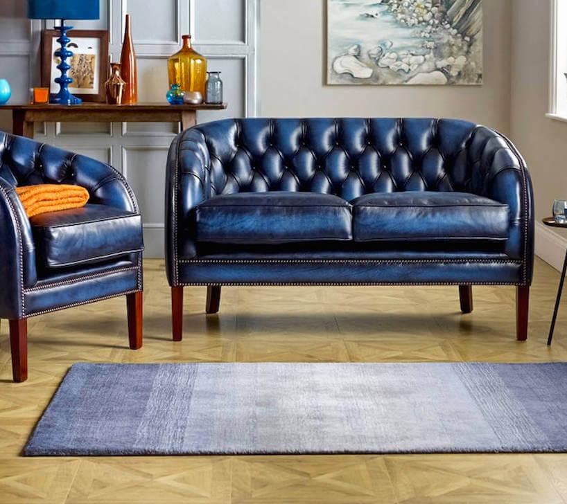 elegancka niebieska plisowana skórzana sofą zfotelem na drewnianej jasnej podłodze zmałym niebieskim dywanem