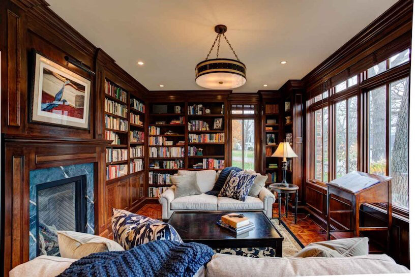 ciemne eleganckie wnętrze wstylu angielskim zdrewnianą zabudową pod książki zbiała małą sofą zciemnym zabytkowym stolikiem