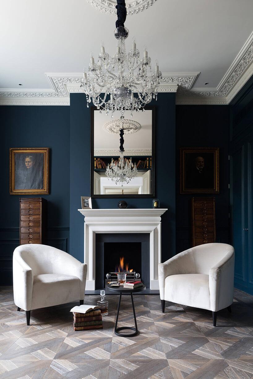 ciemno niebieskie wnętrze wstylu angielskim zdwoma białymi fotelami na tle kominka zbiałą zabudową