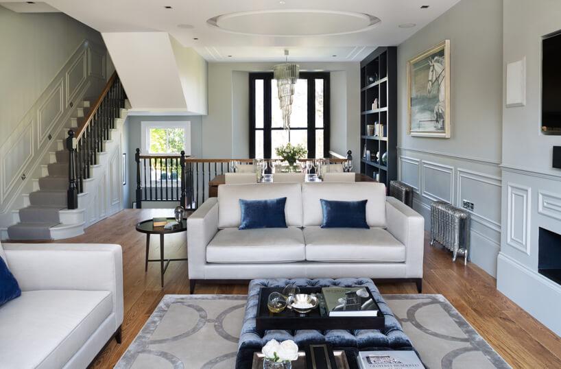 białe eleganckie wnętrze wstylu angielskim zbiałą sofą zdużą niebieską plisowaną pufą