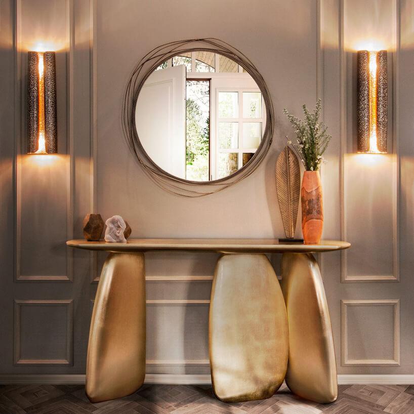 złoty stolik pod ścianą na trzech złotych nogach przypominających kamienie