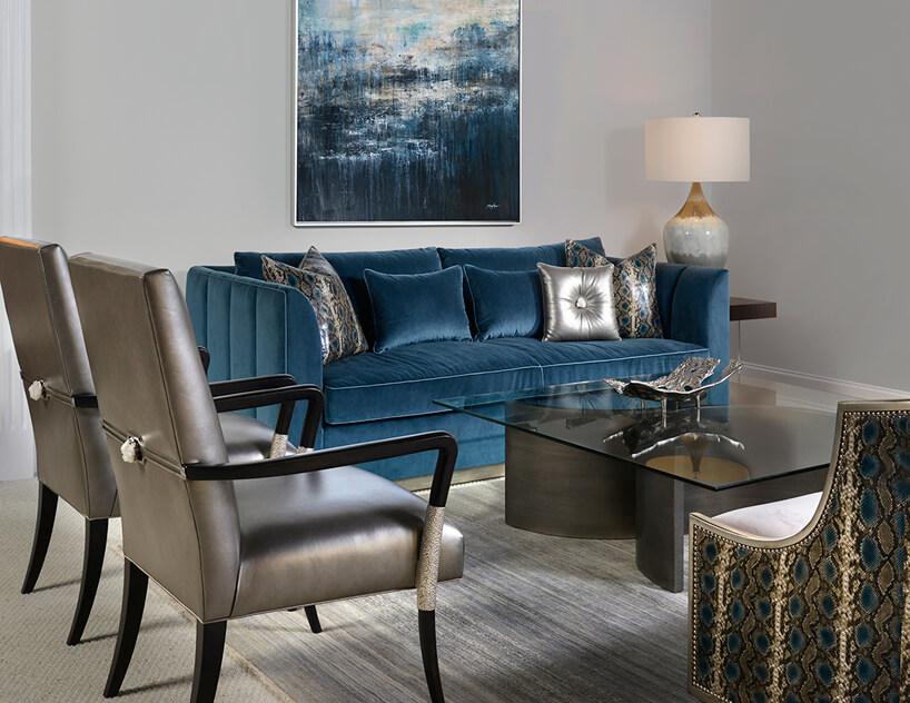 dwa krzesła ze srebrnym siedziskiem ioparciem na czarnych nogach na tle niebieskiej sofy przy dużym szklanym stoliku
