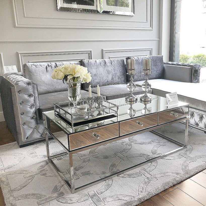 srebrna błyszcząca narożna sofa za szklanym stokiem zbłyszczącą ramą zszufladami