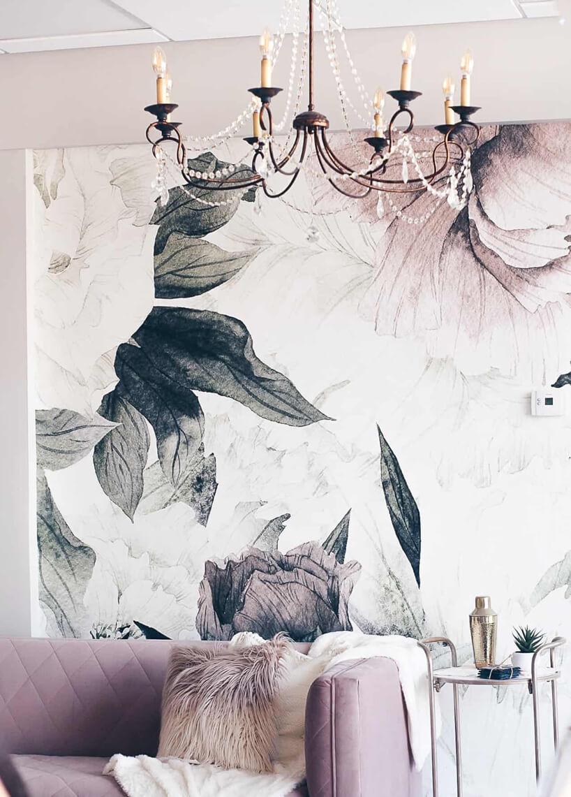 fioletowa sofa obok małego stolika na tle obrazu pod żyrandolem wstarym stylu