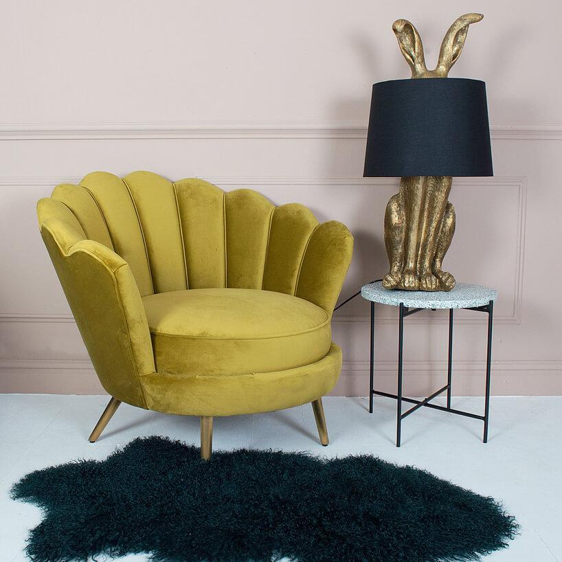 błyszczący żółty fotel obok stolika zdużą lampą wkształcie złotego stolika zczarnym abażurem