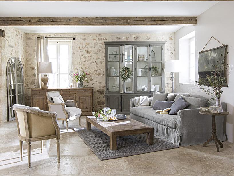 salon wstylu prowansalskim zdużym szarym przeszklonym kredensem na tle ściany zkamieniami