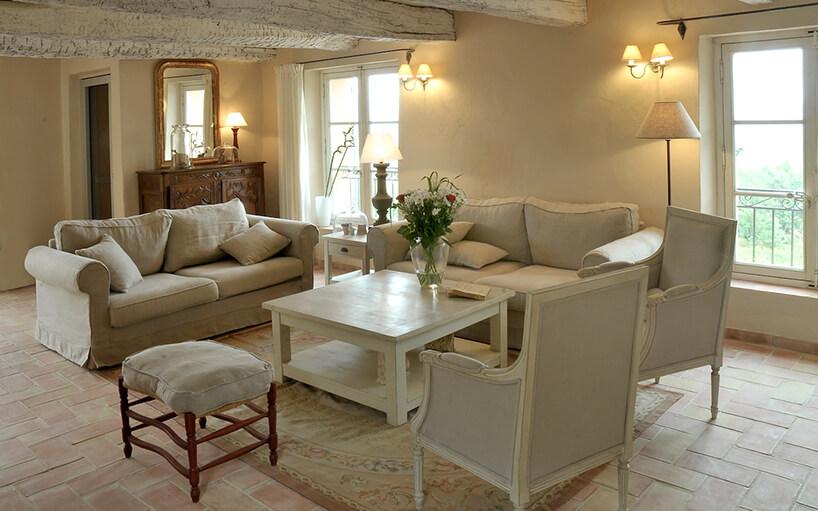 salon wstylu prowansalskim ze starą podłogą zbezowym zestawem drewnianym stolikiem idwoma krzesłami zepoki