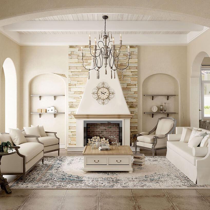 nowy salon wstylu prowansalskim zdużym kominkiem na tle ściany zpiaskowca