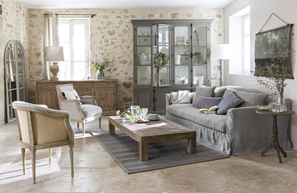 salon w stylu prowansalskim z dużym szarym przeszklonym kredensem na tle ściany z kamieniami