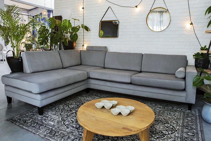 szara sofa narożna Focus od 9Design na krótkich czarnych nóżkach przy drewnianym okrągłym stoliku na szarej podłodze na tle białej ceglanej ściany