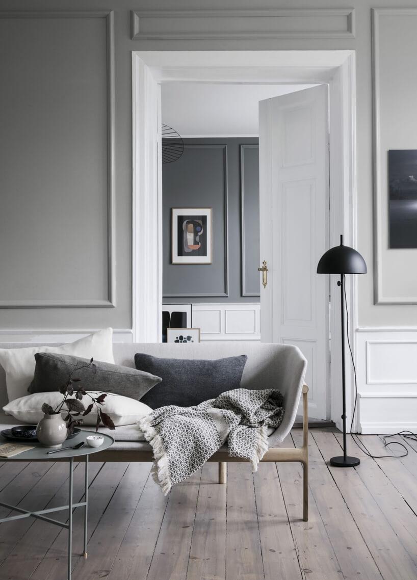 szare wnętrze salonu zbiałymi drzwiami ifutryną jaki tło dla białej sofy na cienkim drewnianym stelażu