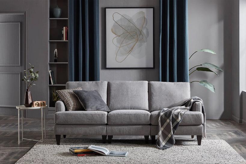 szara trzyczęściowa sofa zwysokimi oparciami na szarymi dywanie ipodłodze na tle szarych ścian salonu