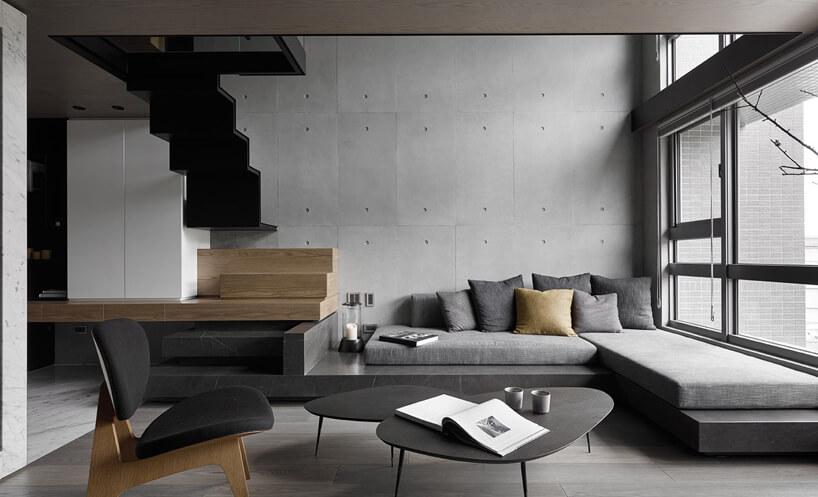 szara sofa narożna wwysokim salonie obok czarnych schodów na antresolę