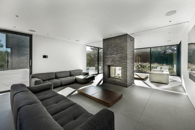 szaro biały przeszklony salon zdwoma szarymi sofami wokół centralnego wyłożonego cegłą kominka