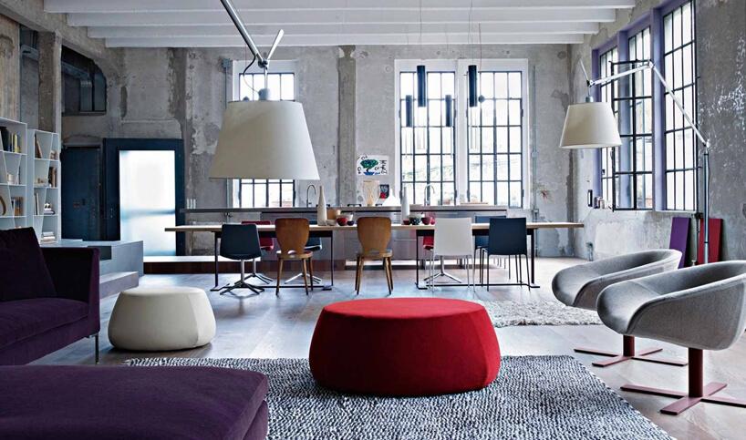 szare betonowe loftowe wnętrze zdrewnianą podłogą iwysokimi metalowymi oknami zmałymi ramkami