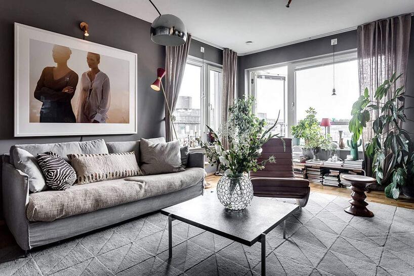 szary salon zdrewnianą podłogą szarą sofą na tle dużych okien