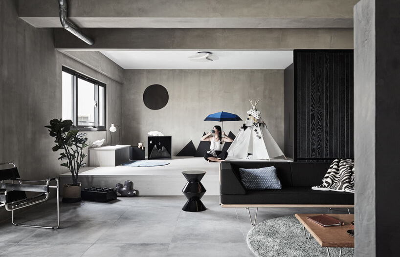 wnętrze salonu zszarą podłoga ścianami isufitem zsofa zczarnym siedziskiem