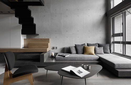 szara sofa narożna w wysokim salonie obok czarnych schodów na antresolę
