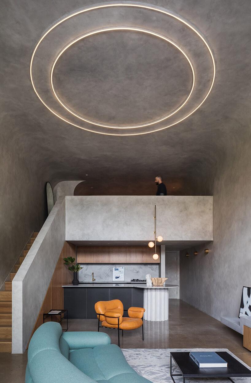 duża antresola wszarym wnętrzu zdrewnianymi schodami nad aneksem kuchennym