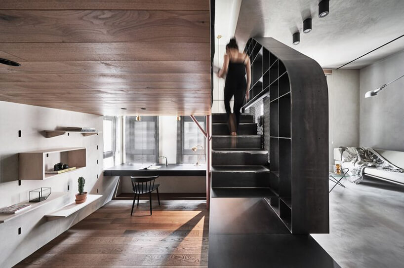 drewniana antresola zciemnymi schodami osłoniętymi szafką zpółkami