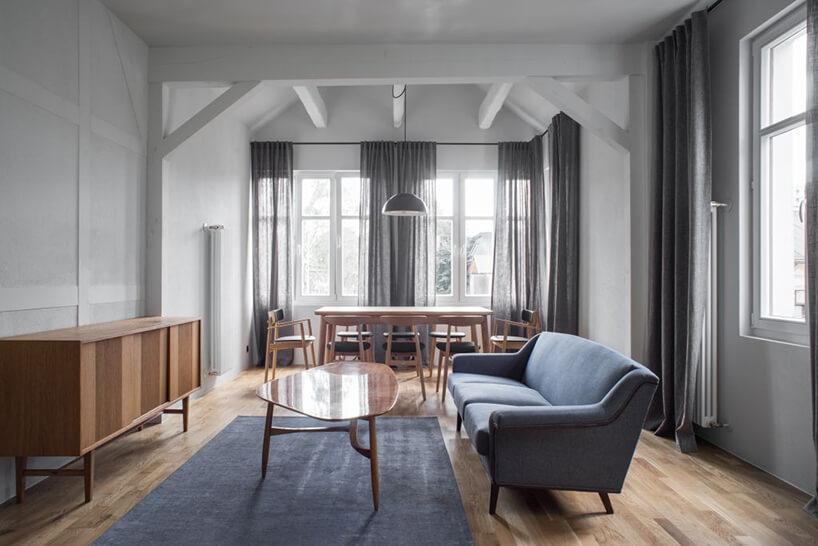 salon zjadalnią - niebieskie sofa przy stoliku onieregularnym blacie na tle drewnianego stołu jadalnego zkrzesłami zniskim oparciem