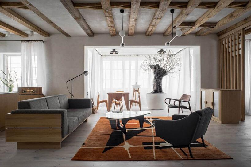 w salonie zjadalnią szara sofa zdrewnianym stelażem na tle białej wnęki zdrewnianym stołem jadalnym zdrewnianym krzesłami
