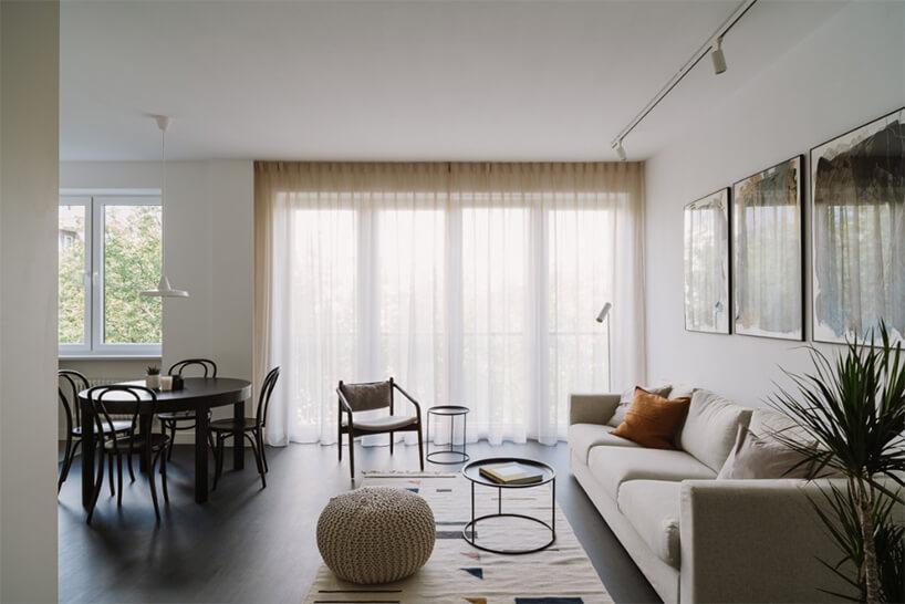 aranżacja salonu zjadalnią beżowa sofa na ciemnej podłodze naprzeciwko wnęki zciemnym okrągłym jadalnym stołem zczterema krzesłami