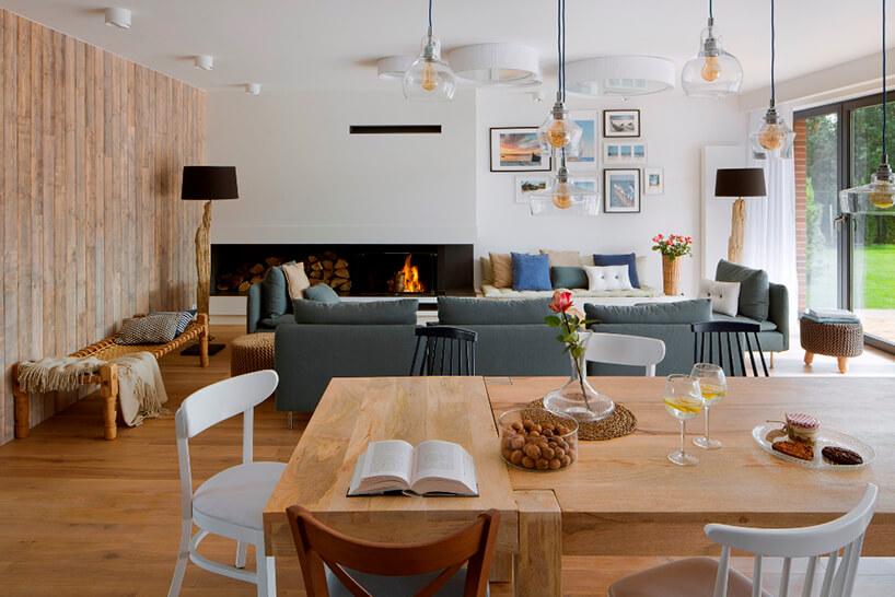 masywny drewniany stół jadalny zkilkoma różnymi krzesłami na tle szarej sofy wsalonie zkominkiem