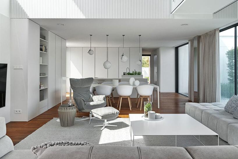 duża narożna sofa zbiałym stolikiem obok szarego fotela zzagłówkiem na tle białego stołu jadalnego zbiałymi krzesłami