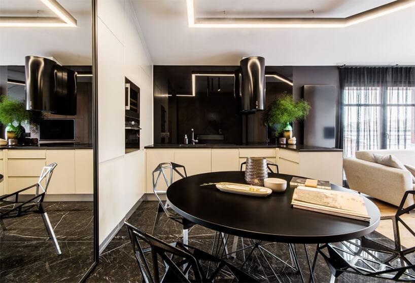 czarny duży okrągłu stół zkrzesłami zwyciętymi trójkątami na tle żółto czarnej kuchni