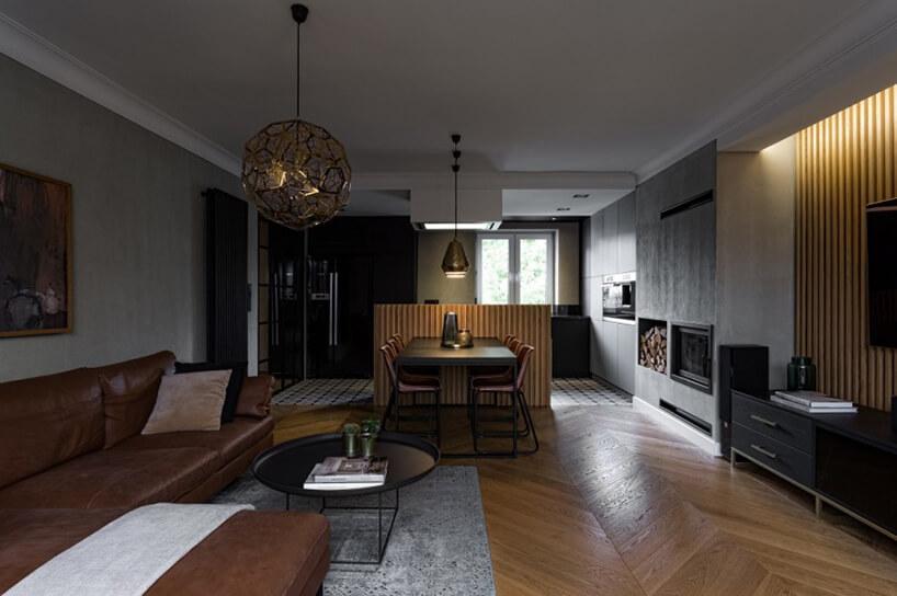 ciemno brązowo sofa narożna przy czarnym metalowym stoliku na tle ciemnego stołu jadalnego
