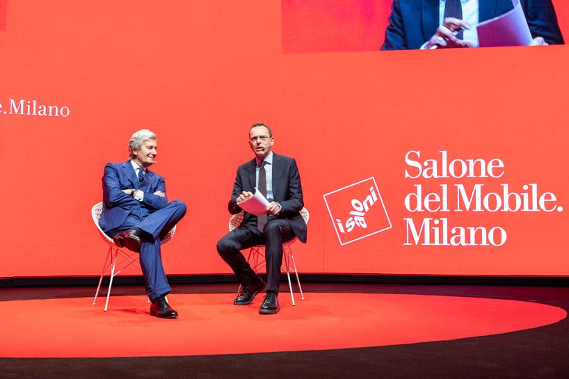dwóch mężczyzn wgarniturach siedzących scenie podczas Salone del Mobile 2019