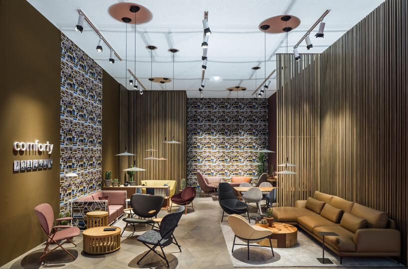 stoisko zdużą brązową sofa oraz wieloma różnymi krzesła od comforty