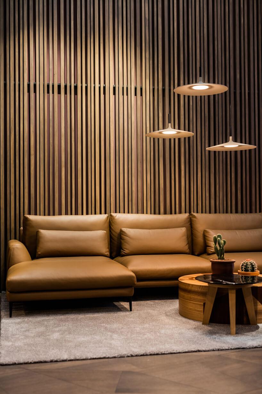 duża brązowa skórzana sofa na tle ściany zdrobnym listewkami