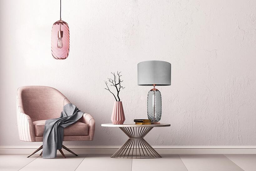 różowy fotel pod różową lampą obok niskiego stolika zlampą iwazonem