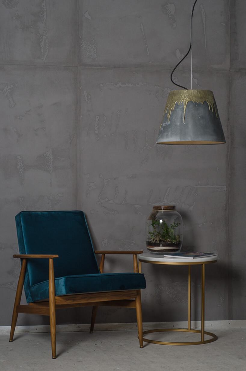 fotel zzielonym obiciem obok stolika ze słojem pod nietypowa szarą lampą