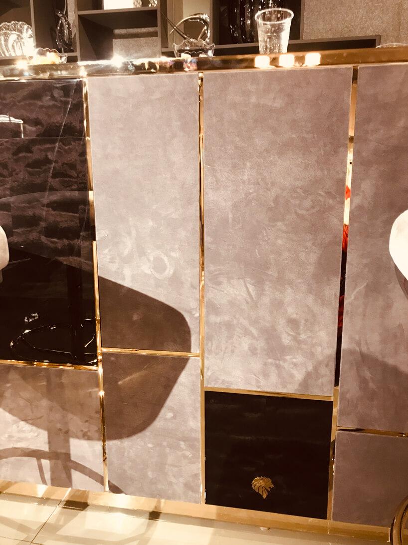 ekskluzywne wyjątkowe wykończenie małego baru wkamienne płyty zelementami złotymi