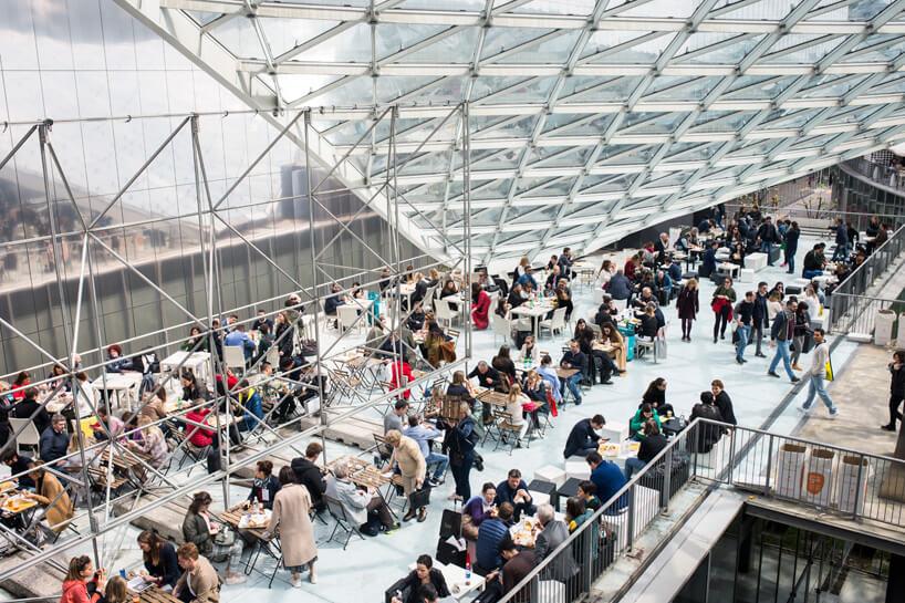 odwiedzający Salone del Mobile.Milano 2019 podczas odpoczynku wprzestrzeni ze stolikami