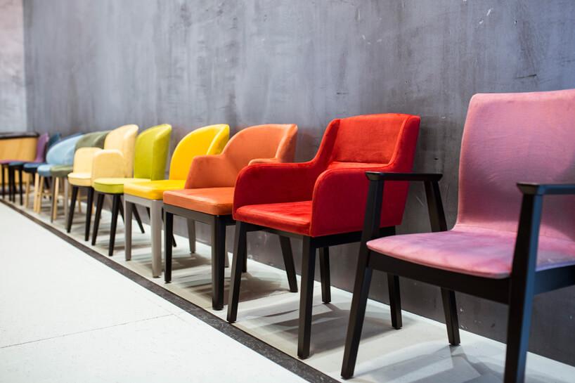 rząd różnokolorowych krzeseł pod szarą ścianą