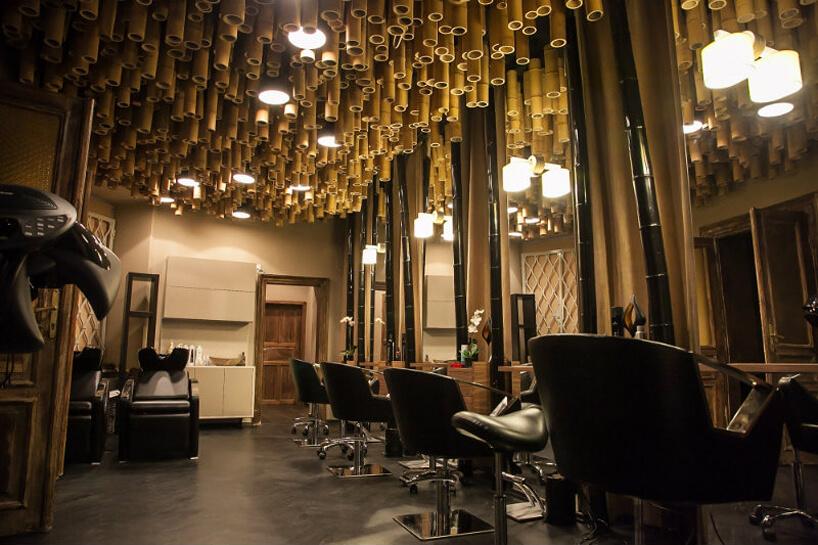 ciemne wnętrze salonu kosmetycznego zpodwieszonymi bambusowymi tykami