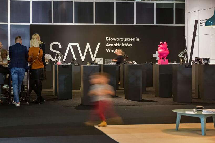 stoisko konkursu SAW podczas Warsaw Home 2019 zróżnymi przedmiotami na podestach an tle białego napisu SAW Stowarzyszenia Architektów Wnętrz