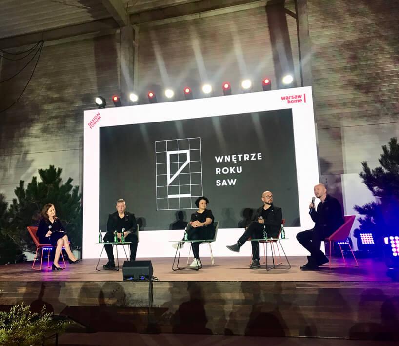 pięć osób na scenie na tle czarnego ekranu zbiały logotypem Wnętrze Roku SAW