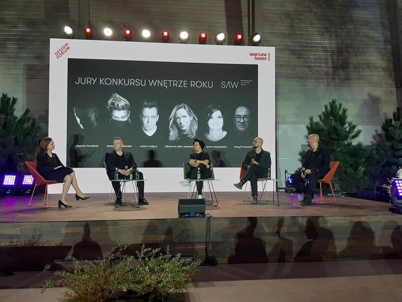 pięć osób na scenie na tle czarnego ekranu ze składem jury konkursu Wnętrze Roku SAW