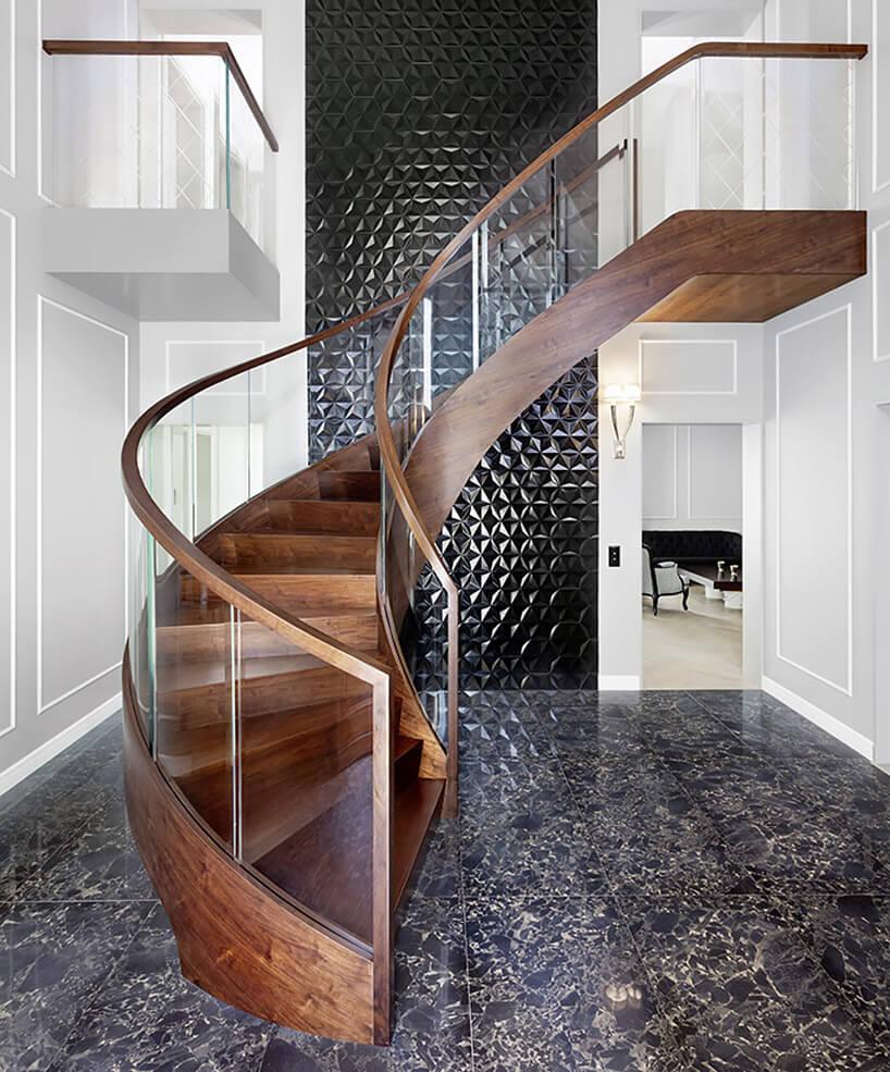 kręcone schody zciemnego drewna iszklana balustradą